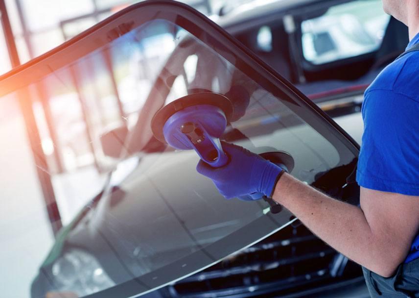 automobile worker replacing windscreen